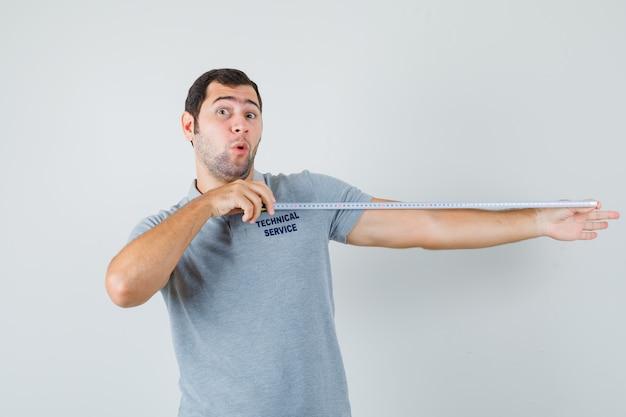 巻尺を使用し、驚いて見える灰色の制服を着た若い技術者。