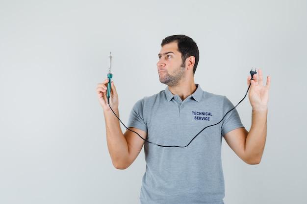 Молодой техник смотрит на отвертку, держа его за руку в серой форме и выглядит сосредоточенным.