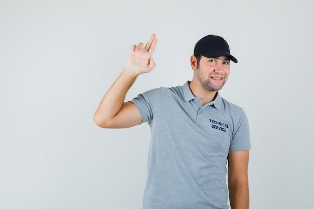 Молодой техник делает знак пальца пистолет в серой форме и выглядит весело.