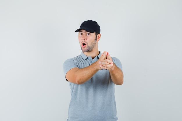 Молодой техник делает знак пальца пистолет в серой форме и выглядит уверенно.