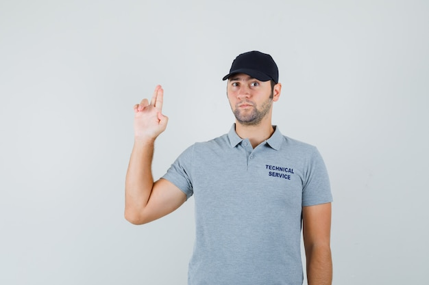 Молодой техник делает знак пальца пистолет в серой форме и смотрит задумчиво.