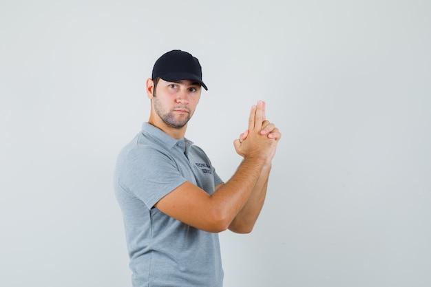 Молодой техник делает знак пальчикового пистолета в серой форме и выглядит строго.