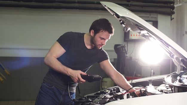 Young technician man making engine service of car in garage.