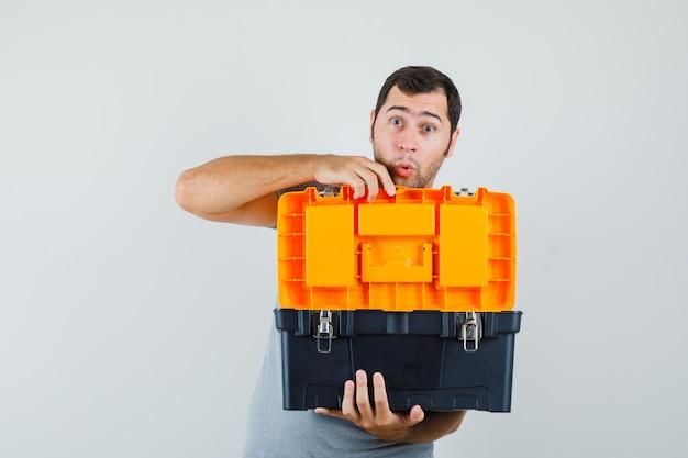 회색 유니폼에 그의 양손으로 도구 상자를 열고 심각한 찾고 젊은 기술자.