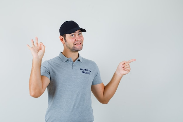 Young technician pointing aside, showing ok sign in grey uniform and looking glad.