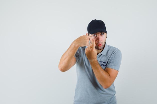 Giovane tecnico che indica la sua palpebra tirata da un dito in uniforme grigia.