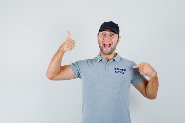 Giovane tecnico che indica la sua maglietta, mostrando il pollice in uniforme e guardando felice.