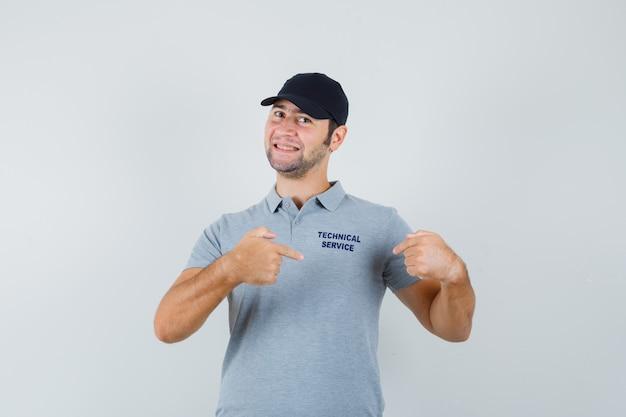 Giovane tecnico che indica la sua maglietta in uniforme e che sembra orgoglioso.