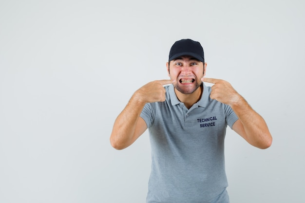 Young technician pointing at his teeth in grey uniform.