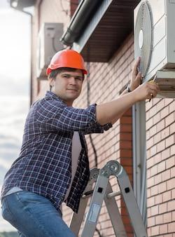 外のエアコンユニットを修理する若い技術者