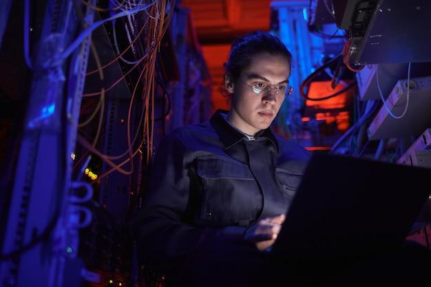 Молодой техник, настраивающий интернет-сеть в серверной комнате
