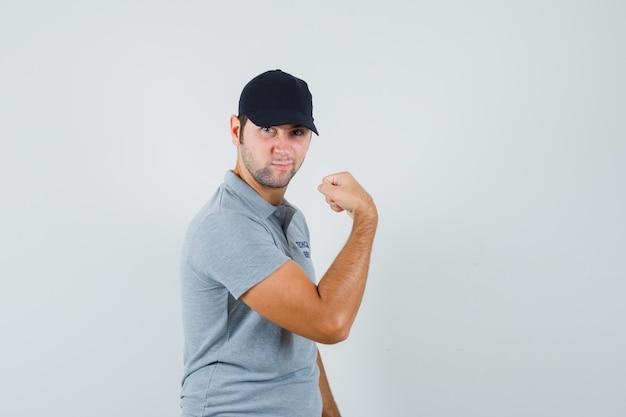 灰色のユニフォームで腕の筋肉を示し、自信を持って見える若い技術者。