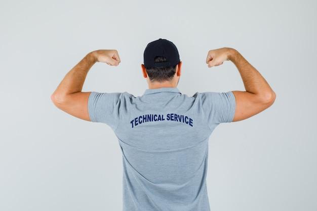회색 제복을 입은 팔 근육을 보여주는 젊은 기술자. 다시보기.
