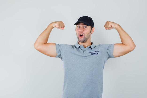 제복을 입은 팔 근육을 보여주는 젊은 기술자.