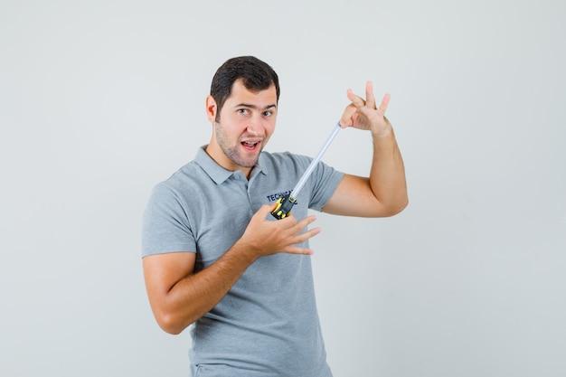 灰色のユニフォームで巻尺を開き、楽観的に見える若い技術者。