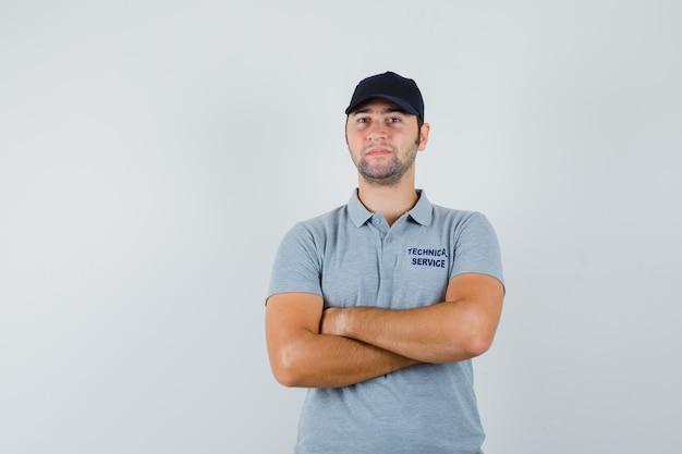 制服を着て腕を組んで立って自信を持って見える若い技術者。