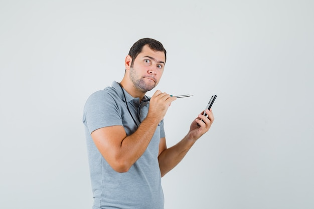Young technician trying to open the back of his smartphone by using drill in grey uniform and looking curious.