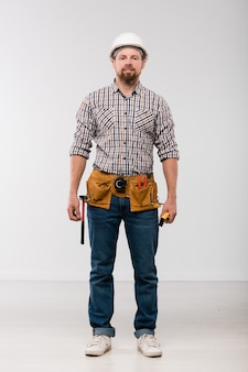 Young technician with toolbelt on his waist standing in front of camera and looking at you in isolation
