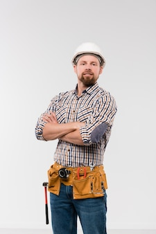 カメラの前に立っている間、胸で腕を組んで腰にツールベルトを持っている若い技術者