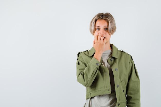 Молодой мальчик-подросток эмоционально кусает ногти в футболке