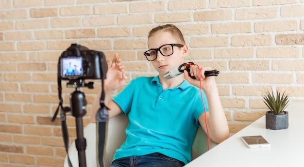 自宅でライブvlogビデオチュートリアルセッションを記録するためのカメラを設定する10代の若い少年ブロガー。 itブログまたはvlog、ソーシャルメディアホビー放送、またはオンライン学習コースのコンセプト
