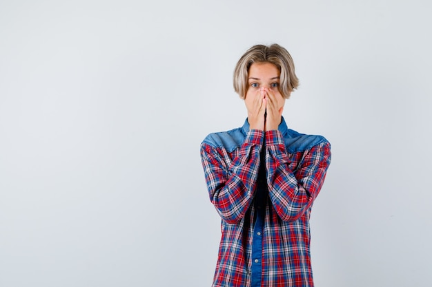 Giovane ragazzo adolescente in camicia a quadri che tiene le mani sulla bocca e sembra spaventato, vista frontale.