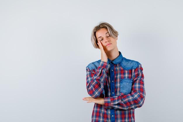Giovane ragazzo adolescente in camicia a quadri che si appoggia la guancia a portata di mano e sembra assonnato, vista frontale.
