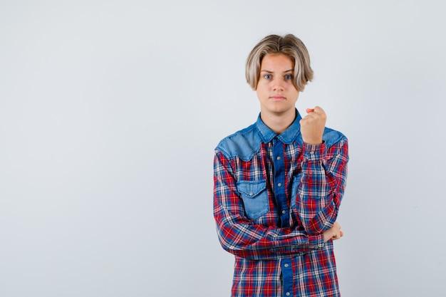 Giovane ragazzo adolescente in camicia a quadri che mostra il pugno chiuso e sembra serio, vista frontale.