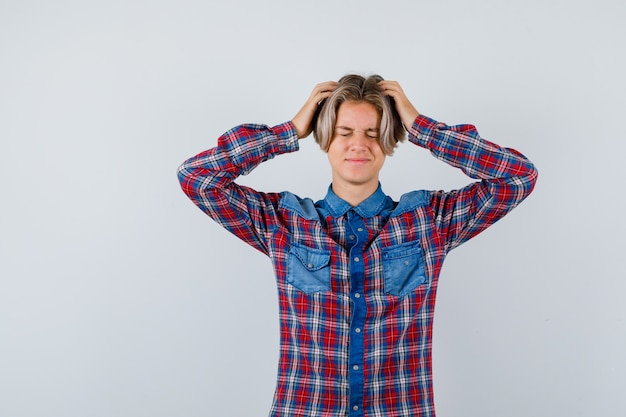 Young teen boy in checked shirt with hands on head and looking distressed