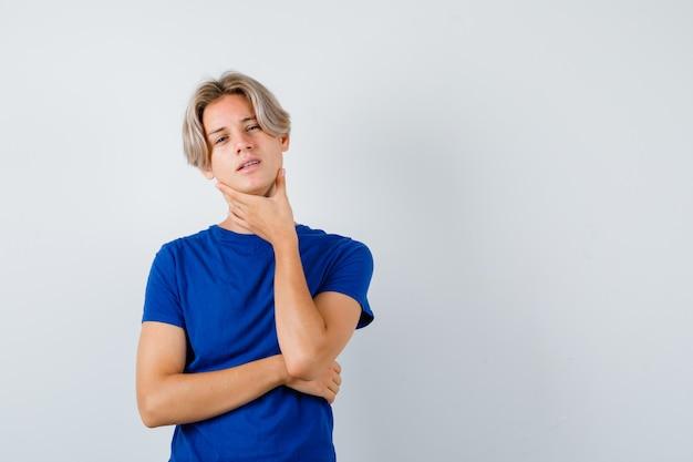 파란색 티셔츠를 입고 목이 아프고 앞이 보이는 어린 10대 소년.