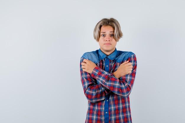 自分を抱きしめ、チェックのシャツを着て冷たく感じ、無力に見える若い十代の少年。正面図。