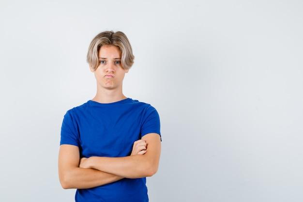 파란색 티셔츠를 입은 어린 십대 소년이 팔짱을 끼고 불쾌한 표정을 짓고 있습니다.