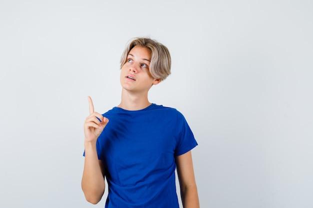 파란색 티셔츠를 입은 어린 10대 소년이 위쪽을 가리키고 희망적인 앞모습을 보고 있습니다.
