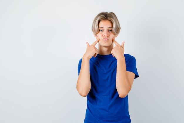 파란색 티셔츠를 입은 어린 10대 소년이 뺨에 손가락을 대고 음울한 앞모습을 보고 있습니다.