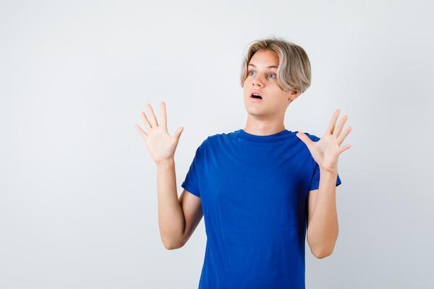 降伏のジェスチャーを示し、おびえた、正面図を示す青いtシャツの若い10代の少年。