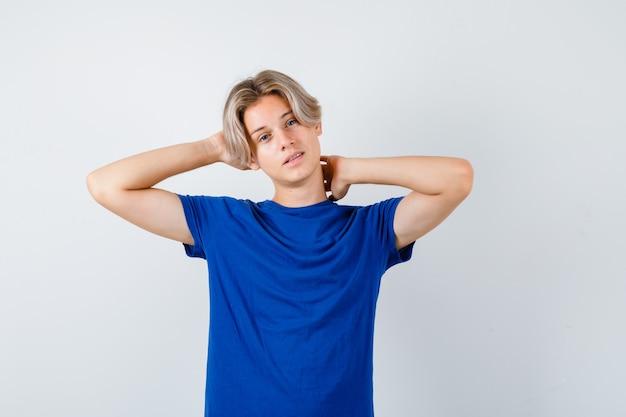 파란색 티셔츠를 입은 어린 십대 소년은 머리와 목 뒤에 손을 얹고 주저하며 정면을 바라보고 있습니다.