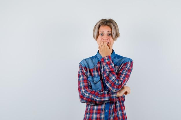 チェックシャツを着た若い10代の少年は、感情的に爪を噛み、不安そうに見えます