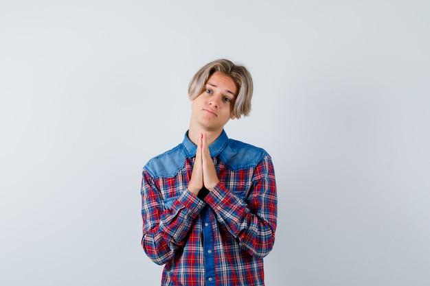 チェックシャツを着た若い10代の少年は、祈りのジェスチャーで手を保ち、希望に満ちた正面図を探しています。
