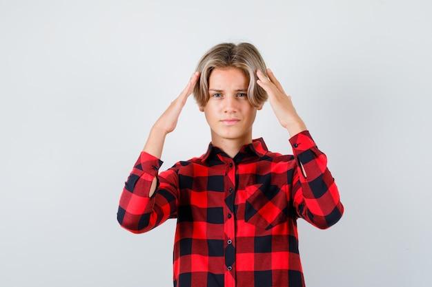 체크 셔츠를 입은 어린 십대 소년이 머리에 손을 얹고 어리둥절한 표정을 짓고 있습니다.