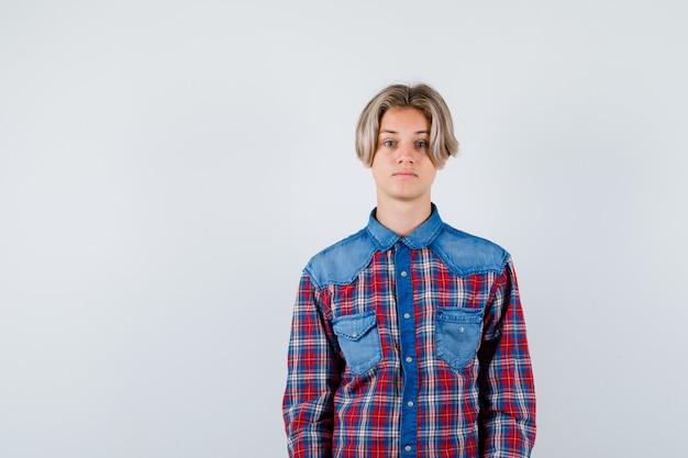 カメラを見て、真剣に見えるチェックシャツの若い十代の少年