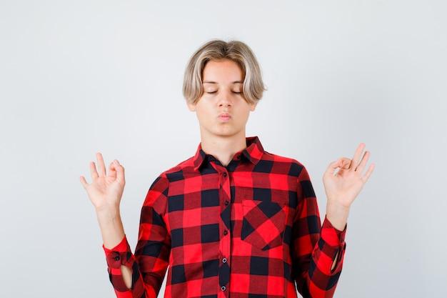 瞑想のジェスチャーを示し、リラックスした、正面図を示すチェックシャツを着た若い十代の少年。