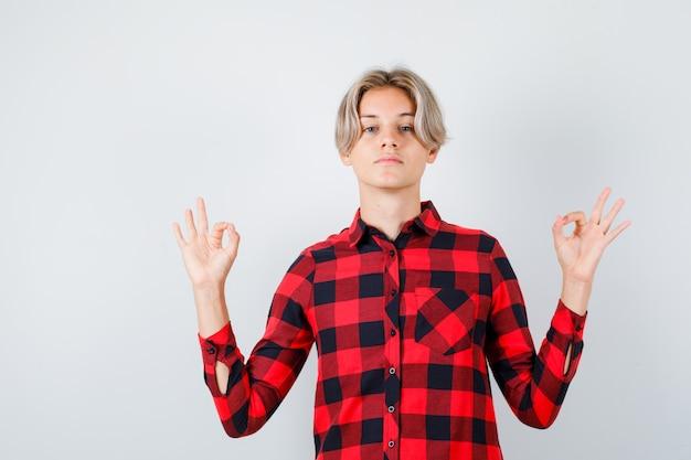 チェックシャツを着た若い10代の少年は、ヨガのジェスチャーを示し、リラックスして、正面図を表示します。