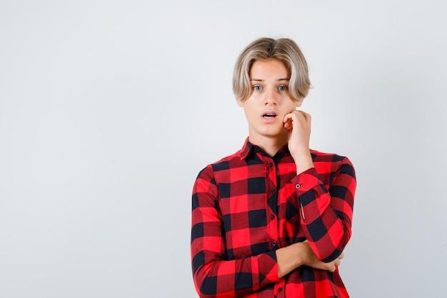 체크 셔츠를 입은 어린 10대 소년이 턱을 만지고 혼란스러워 보이는 앞모습.