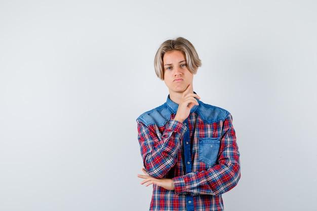 チェックシャツを着た少年が指で顎に触れ、思慮深く見える