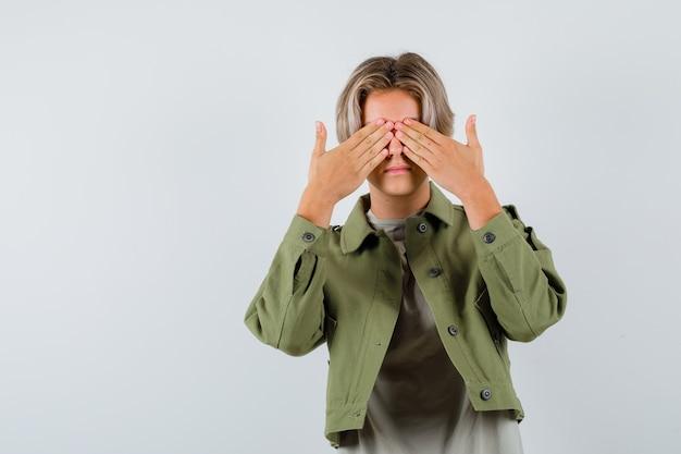 손으로 눈을 가리고 무서워 보이는 녹색 재킷에 어린 십대 소년