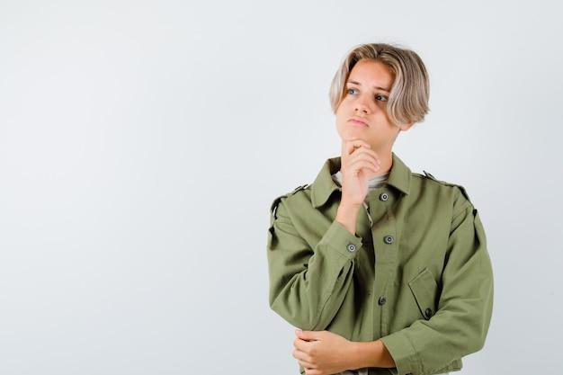 手で顎を支える緑のジャケットの若い十代の少年