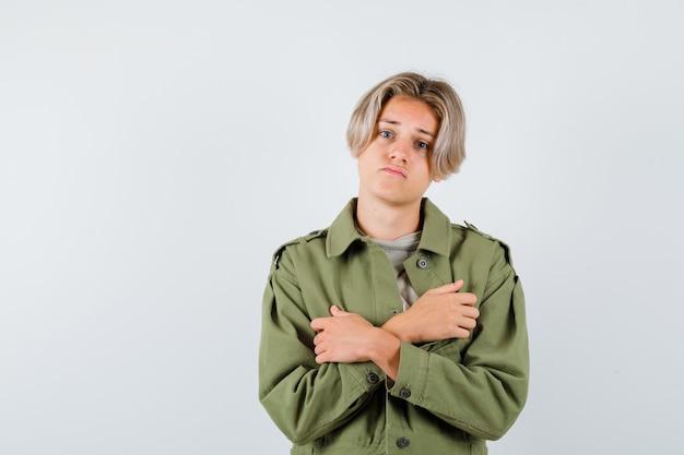 胸に腕を組んで失望しているように見える緑色のジャケットの若い10代の少年