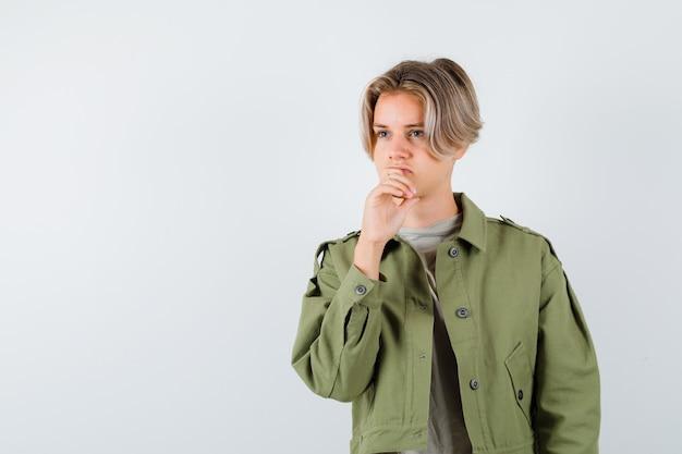 あごに手で緑のジャケットの若い十代の少年