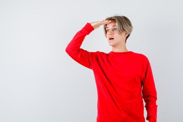 赤いセーターを着た若い10代の少年は、頭上に手を渡して遠くを見て、不思議に思って、正面図を探しています。
