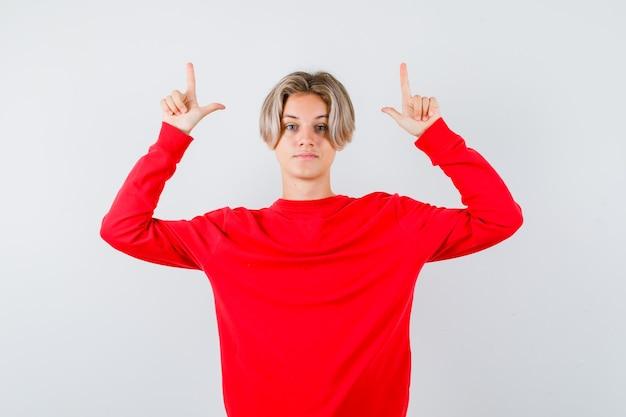 빨간 스웨터를 입은 어린 10대 소년이 위를 가리키고 자신감 있고 앞모습을 보고 있습니다.